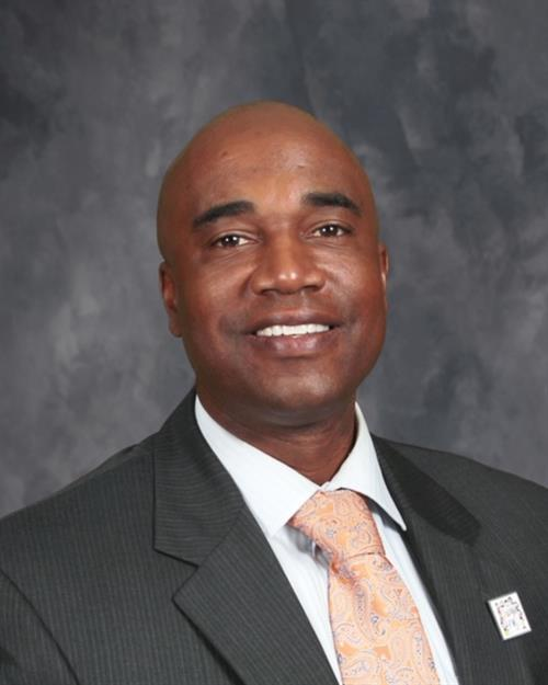 A headshot of principal Frank Williams wearing a suit and tie.