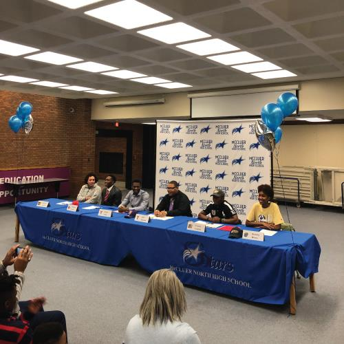 An image of six student athletes sitting at a table signing letters to attend their chosen universit