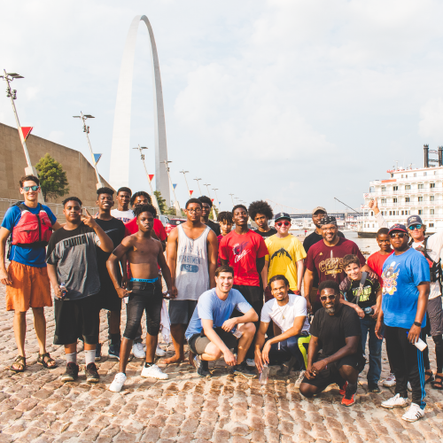 A group photo of the young men a part of the mentoring program standing at the riverfront .